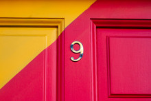 House Number Nine On A Brightly Painted Red And Yellow Wooden House Door With A Diagonal Stripe And The 9 In Bronze