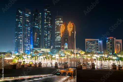 Tuinposter Dubai Skyscrapers of Abu Dhabi at night with Etihad Towers buildings. Abu Dhabi is the capital and the second most populous city of the United Arab Emirates.