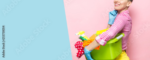 Fotografía  Young woman holding cleaning tools and products in bucket, isolated on white