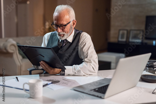 Garden Poster Nostalgic mature businessman looking at picture frame at his office desk.