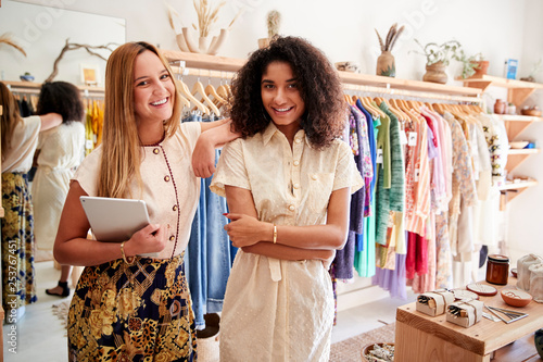 Fotografía  Portrait Of Two Female Sales Assistants With Digital Tablet Working In Clothing
