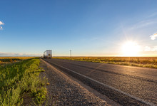 A Truck Travels Along An Empty Long Straight Road In The New South Wales Countryside On A Blue Sky Day At Sunset.