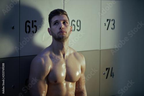 Fototapeta  Sweaty pensive athletic man sitting in gym's dressing room.