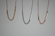 Golden, Rose Gold And Metallic Necklace On White Background
