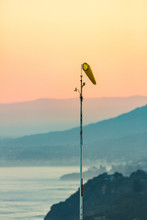 An Aviation Hang Gliding Navigational Wind Sock Blows In A Light Wind Breeze Along The Coast At Sunset With Aerial Perspective Hills. New South Wales, Australia.
