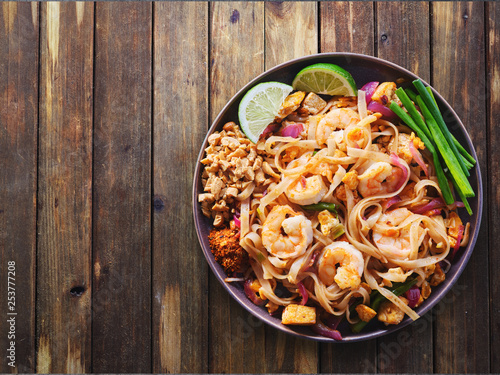shrimp pad thai on plate in flat lay composition with copy space atop rustic woo Wallpaper Mural