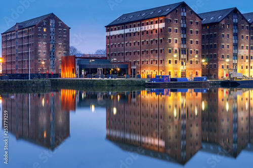 Vászonkép  Gloucester docks warehouses reflected in quay on Sharpness Canal