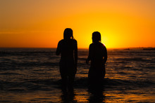 Two Girls Stand In The Ocean