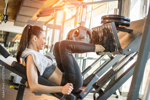 Side view of fit young sportswoman flexing her leg's muscles on exercise machine Tableau sur Toile