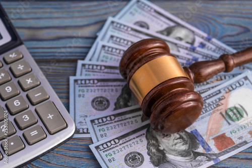 The judge's gavel, calculator, banknotes of American dollars on the background of wooden table. business, Finance. corruption.