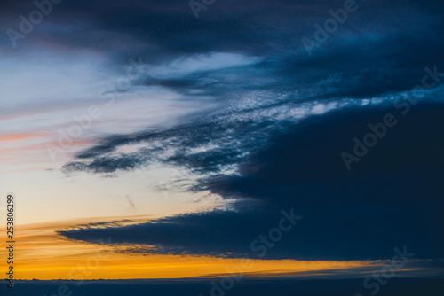 In de dag Zwavel geel Amazing dramatic blue cloudy sky with orange sunshine in clouds. Atmospheric background in overcast weather. Storm warning. Beautiful dark cloudscape. Sunset. Sunrise. Dawn. Copy space.