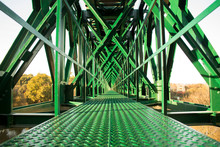 Metal Structure Of Railway Bridge, Railway With Vanishing Point In The Center. Trees On The Background Outside The Bridge