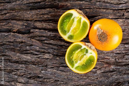 Fotografía  Fruit of lulo on tree bark (Solanum quitoense)