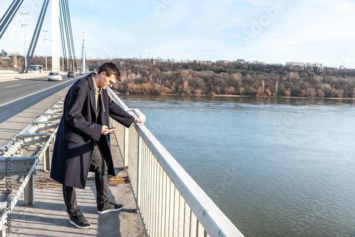 Fotografie, Tablou  Depressed and anxious man standing on the bridge with suicidal thoughts disappoi