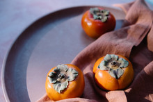 Persimmons On Terracotta And Linen