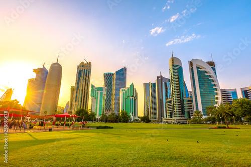 Fényképezés  Doha West Bay high rises at sunset from green lawn of a park along corchiche promenade