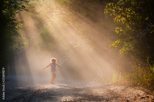 Cadres-photo bureau Jogging Young woman in the sun on a forest road. A girl is dancing in the forest. Bright emotion.