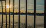 Sun flares through the railing and reflection on the frozen river