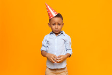 Picture Of Frustrated Unhappy Afro American Little Boy Wearing Red Cone Hat Having Mournful Upset Facial Expression, Making Nervous Gesture After Being Told By His Father For Misbehavior At Party