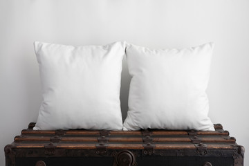 Mockup of two large white square cushions sitting on an old vintage suitcase
