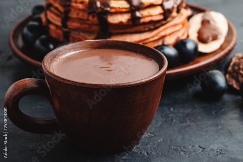 Spoed Fotobehang Chocolade Hot chocolate drink in a cup and pancakes with banana, chocolate sauce and grapes in plate, on dark background