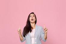 Portrait Of Amazed Young Woman In Striped Jacket Looking, Pointing Index Fingers Up Isolated On Pink Pastel Wall Background In Studio. People Sincere Emotions, Lifestyle Concept. Mock Up Copy Space.