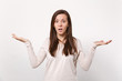 Portrait of shocked perplexed young woman in light clothes spreading and pointing hands aside isolated on white background in studio. People sincere emotions, lifestyle concept. Mock up copy space.