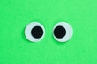 canvas print picture - Cross-eyed googly eyes on neon green background. Mad funny toys eyes close up.