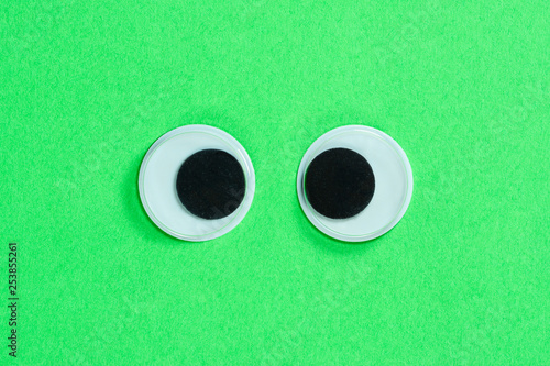 Poster Golf Cross-eyed googly eyes on neon green background. Mad funny toys eyes close up.