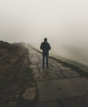A Lone Figure Stands Looking Into The Fog Along A Path On The Mam Tor Hill In The Peak District, UK