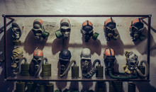 Many Vintage Old Gas Masks On Wall In Bomb Shelter