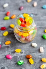 Glass Of Colorful Sweet Jellybeans On Gray Background