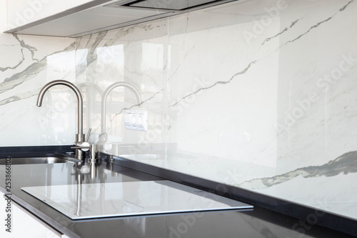 Fototapeta Close up of white glossy kitchen with black quartz countertop and marble tile backsplash. Build-in hidden incorporated hood and undermounted sink.  obraz