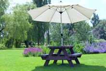 Relaxing Setting In A Pub Garden With Umbrella Sitting Bench Next To Flowers In Bloom, Willow Trees, Al Fresco Dining In An English Countryside On A Sunny Summer Day .