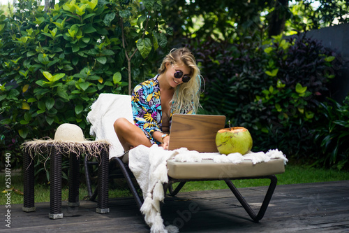 Woman freelancer, travel blogger works on a laptop Wallpaper Mural