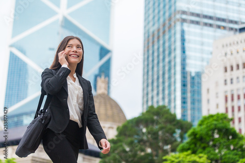 obraz PCV Asian businesswoman talking on mobile phone walking in Hong Kong city street to office, skyscrapers cityscape background. Young woman on smartphone happy. Multiracial Chinese Caucasian lady.