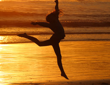 Silhouette Of A Young Girl Jumping In The Sunset