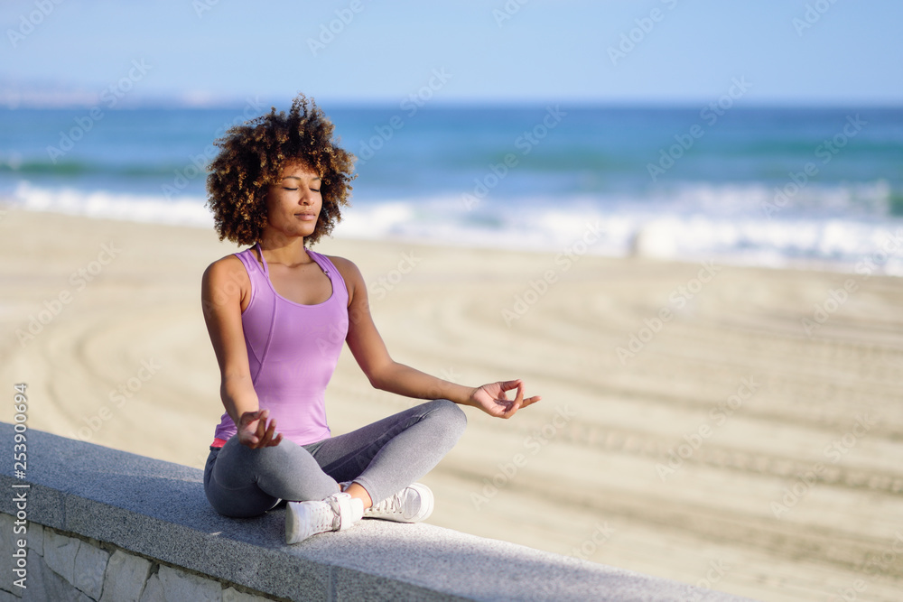 Fototapety, obrazy: Black woman, afro hairstyle, in lotus pose with eyes closed in the beach