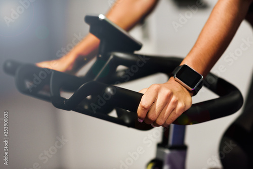 Photo Woman at a gym doing spinning or cyclo indoor with smart watch