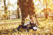 Little Beautiful Dark-skinned Girl Sitting In The Autumn Park With Her European Little Friend