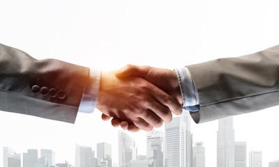 Biznesowy uścisk dłoni jako pomysł na jedność i współpracę lub powitanie. Różne środki przekazu