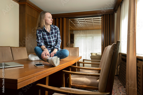 Fotografía  Arbeitsplatz im Wandel der Zeit, junge moderne Frau sitzt auf Konferenztisch in