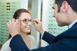 woman in opticians trying on glasses