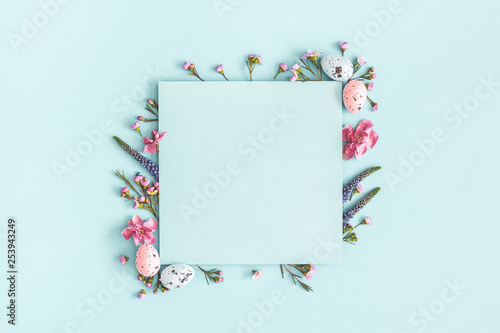 Stickers pour porte Pierre, Sable Easter composition. Easter eggs, flowers, paper blank on pastel blue background. Flat lay, top view, copy space