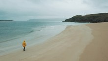 Lonely Man In A Yellow Jacket Walking On A Abandoned Beach While Rain Is Pouring Down On Him