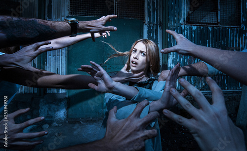 Fotografie, Obraz  Horror. Many zombie hands are drawn to a scared girl