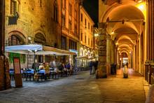 Old Narrow Street With Arcade In Bologna, Emilia Romagna, Italy. Night Cityscape Of Bologna.
