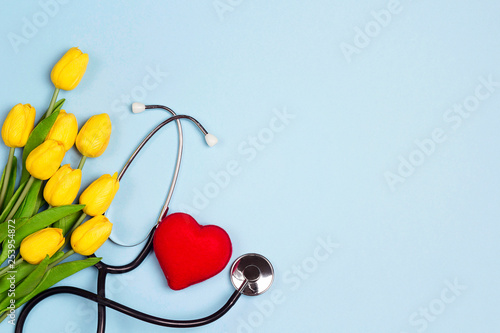 Fotografia Bunch of yellow tulips with stethoscope and heart on blue background