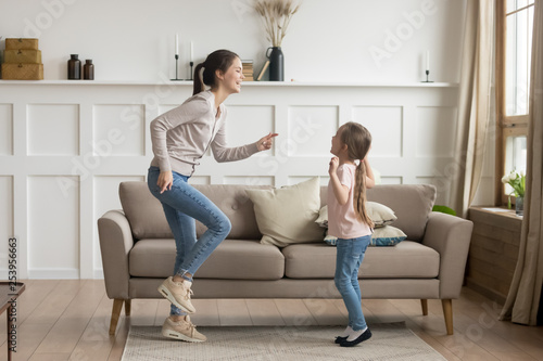 Happy mom and little kid daughter laughing dancing at home - 253956663
