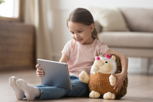 Curious Child Girl Having Fun Using Digital Tablet Embracing Toy